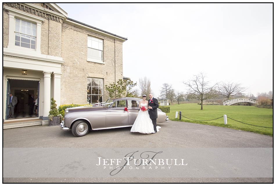 Bride and Groom by wedding car at the Fennes