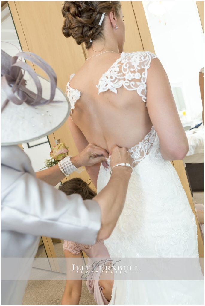 Mum doing up Bride's Dress