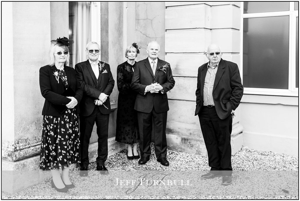 Guests Waiting for Photographs Down Hall Wedding