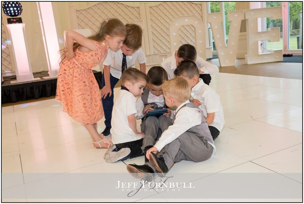 Children sitting on the dance floor at a wedding