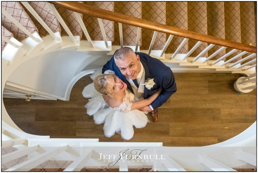 Bride and Groom Botton of Stairs looking up