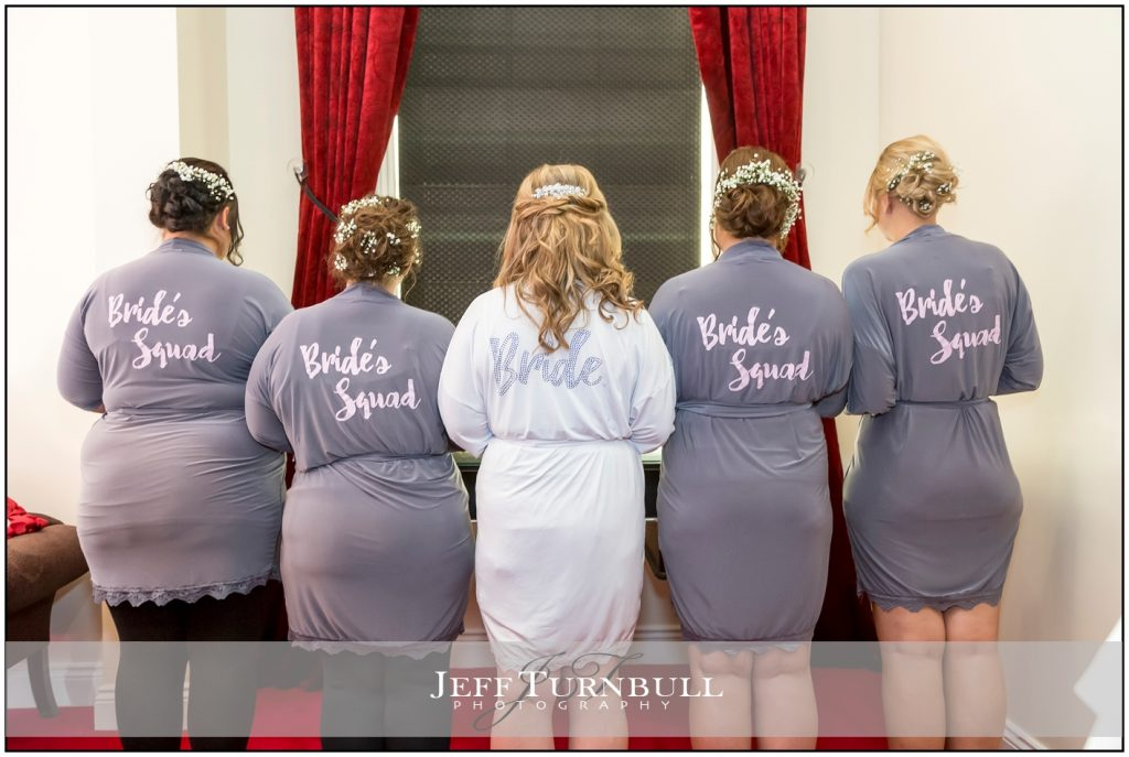 "Bride and bridesmaids in dressing gowns with ""Bride's Squad"""