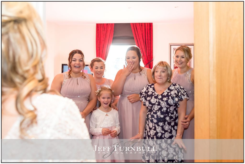 Bride showing herself to bridesmaids