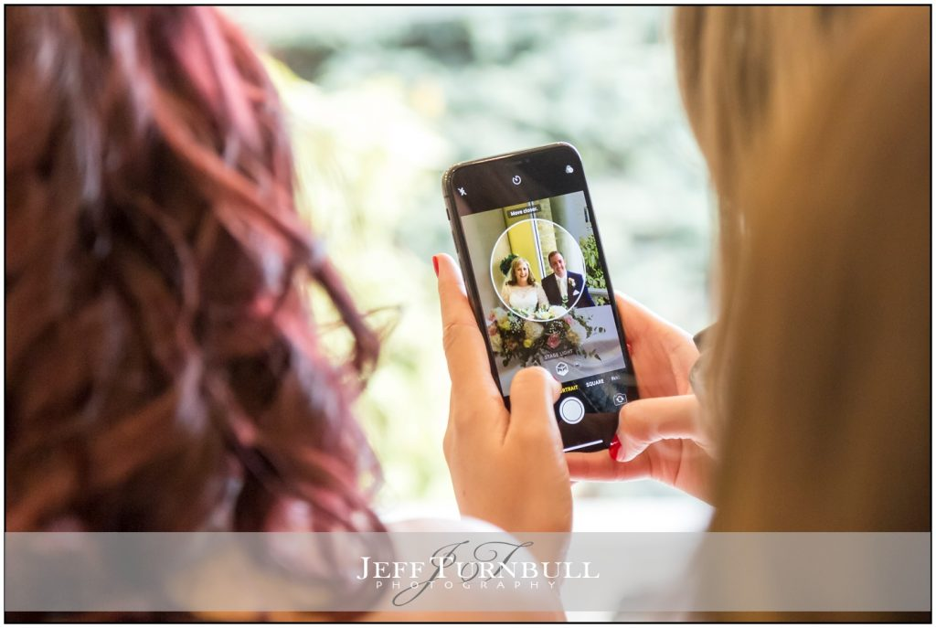 Guest taking wedding photograph on her smart phone