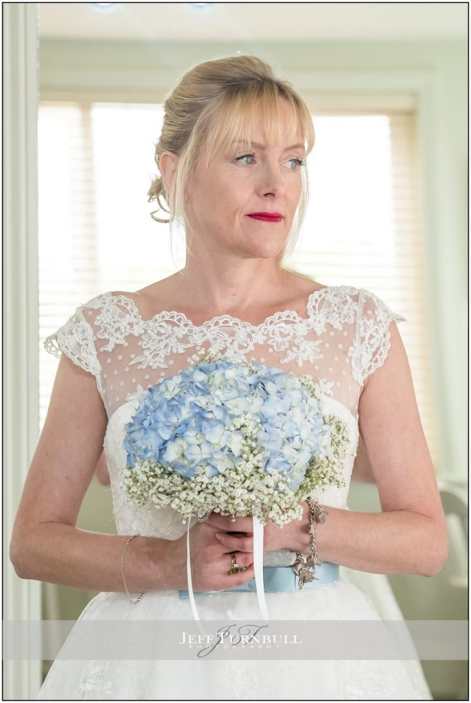 Bride holding blue and white bouquet