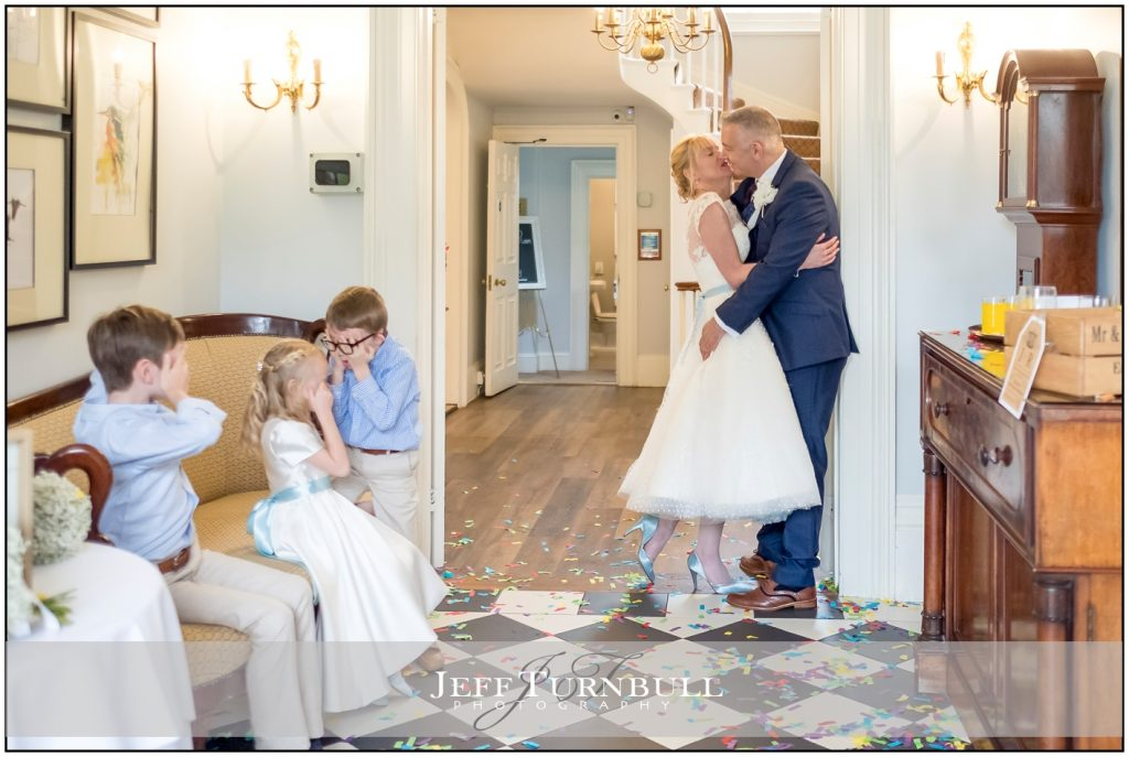 Bride and Groom kissing in front of children