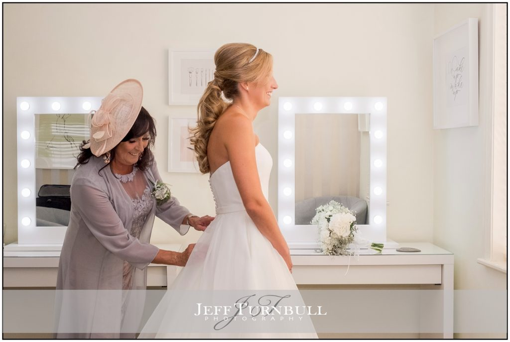 Mum helping bride into dress