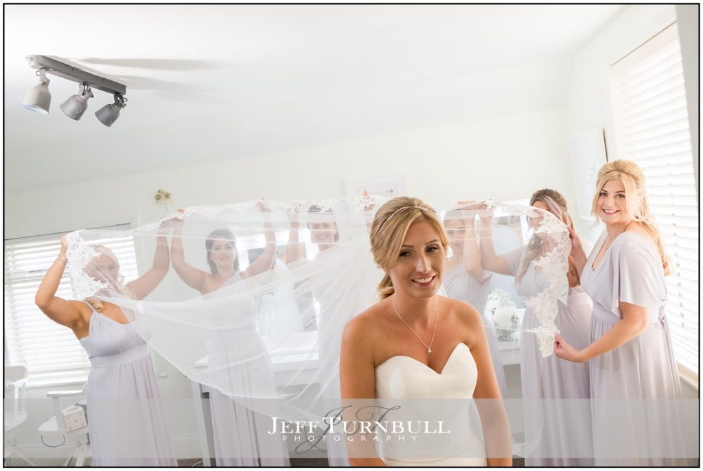 Bridesmaids hold bride's veil