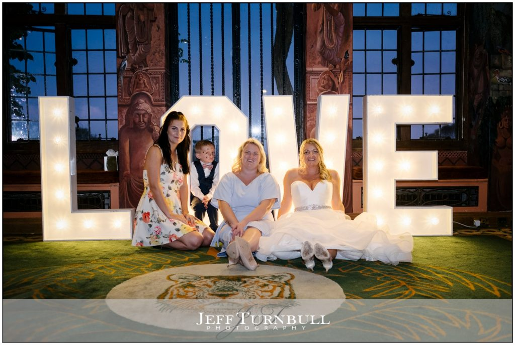 Bride with Friends by Love Sign