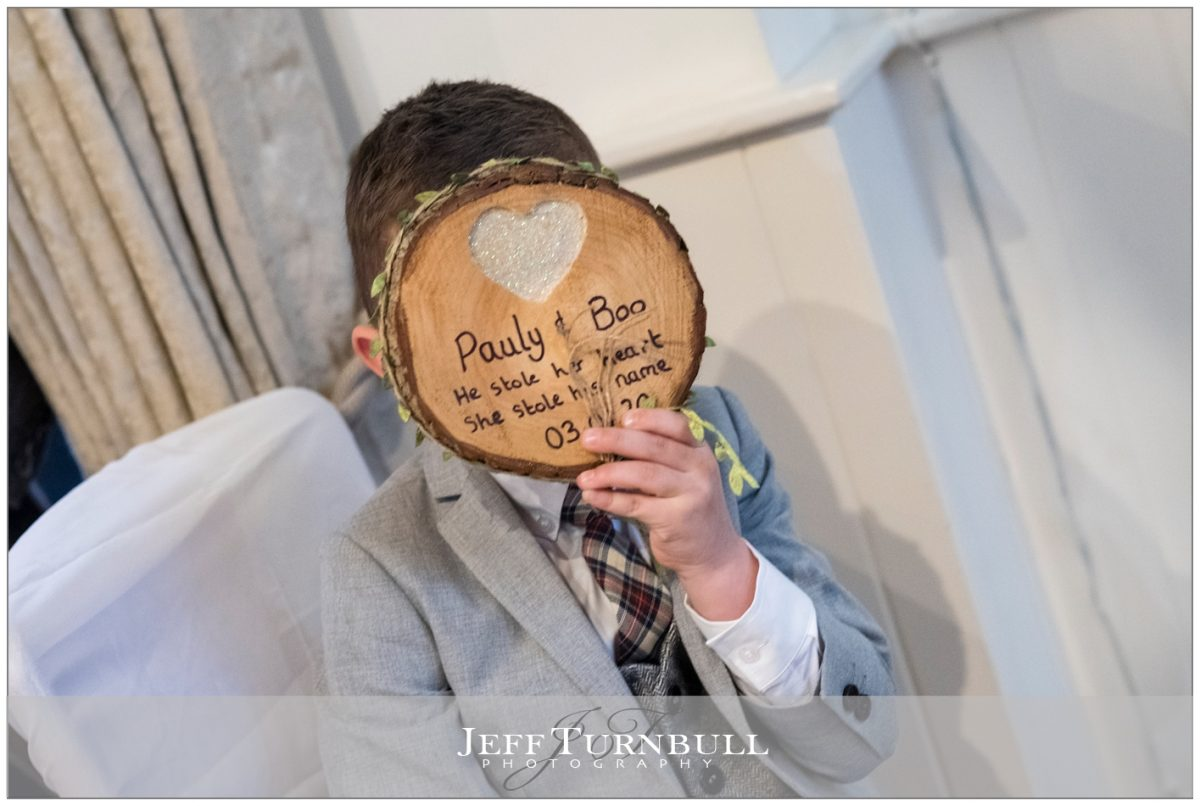 The pageboy hiding behind some wood