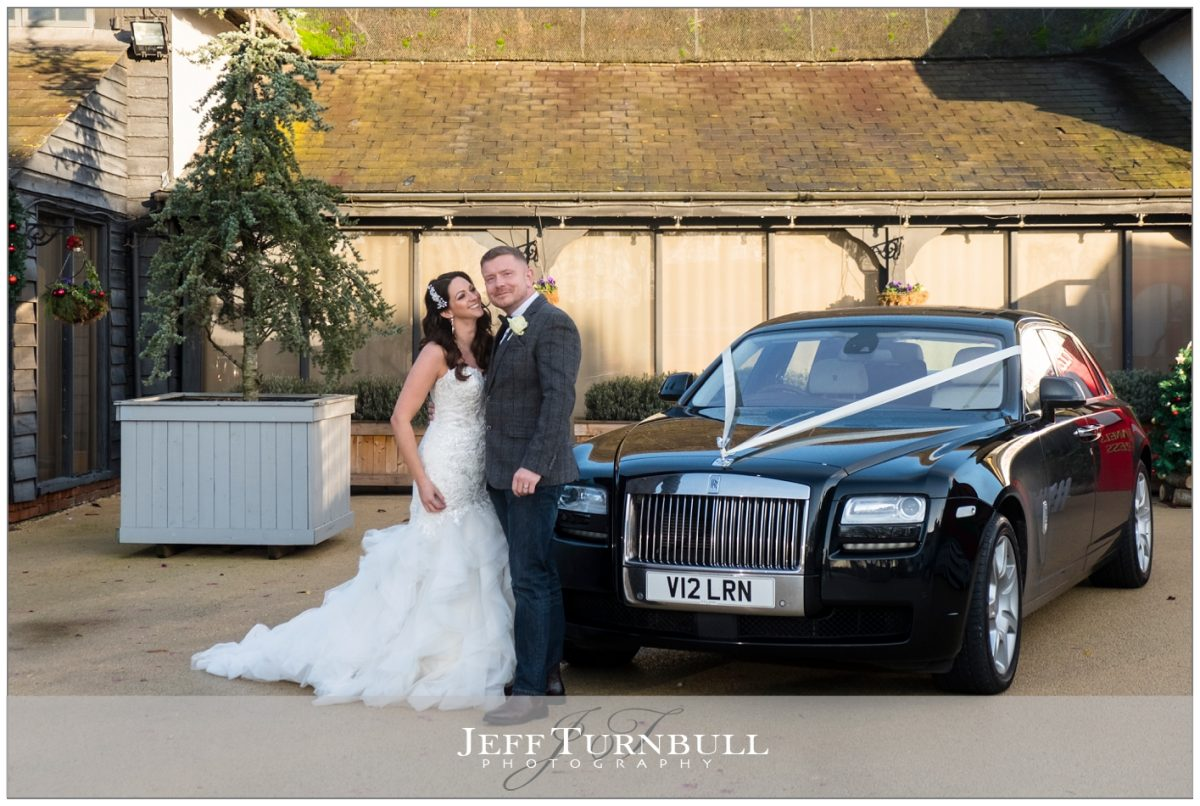 Bride and groom next to Rolls-Royce in front of the barn