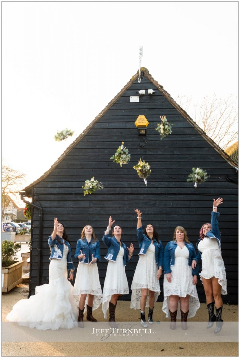 Bride and bridesmaids throw bouquets in the air