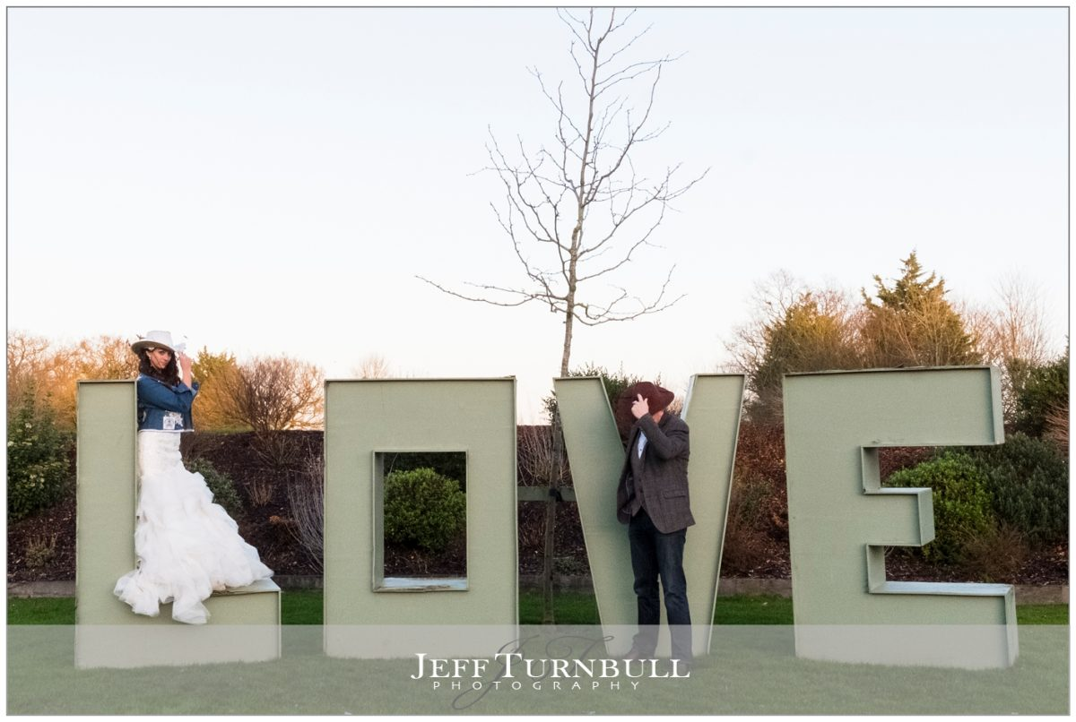 Bride and Groom wearing western style clothing in front of a love sign