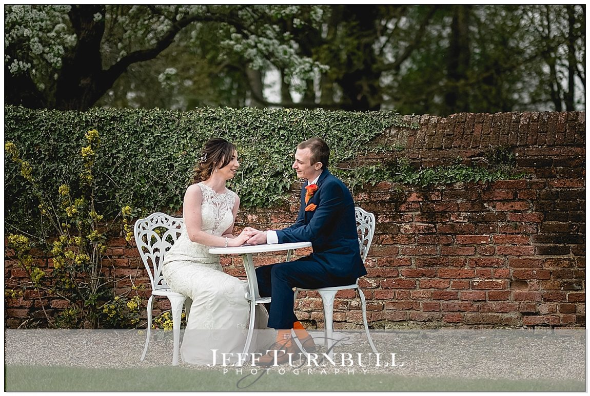 Bride and Groom Sitting at the Table Holding Hands