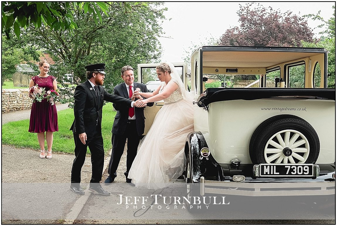 Bride getting out of vintage wedding car